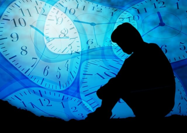 歪んだ時計を背景に項垂れて座る男性のシルエット