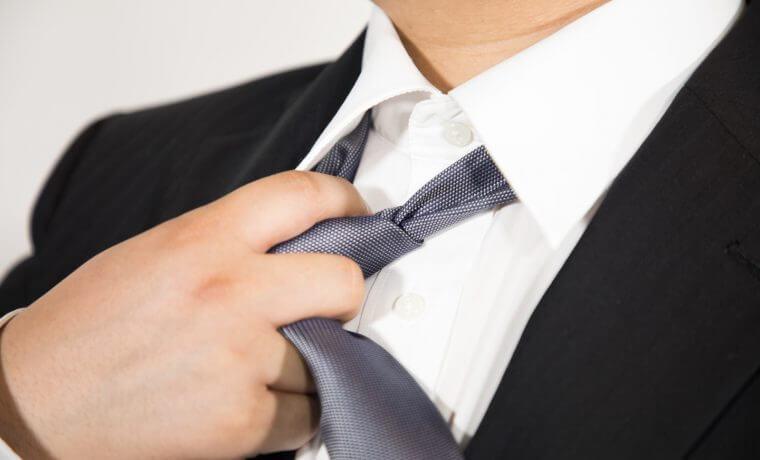 スーツのネクタイを緩める男性