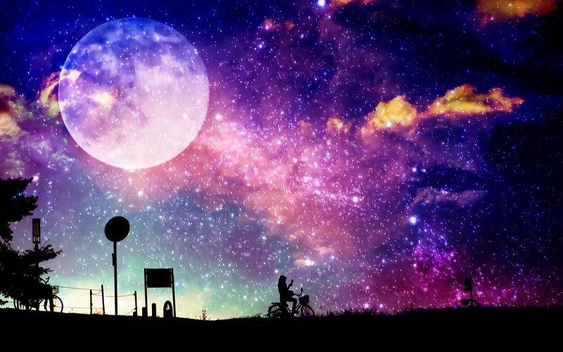 月をバックに自転車に漕ぐ人