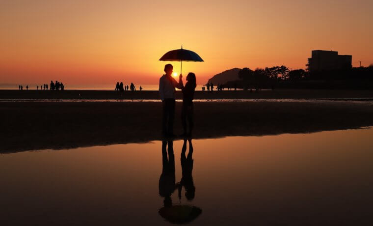 夕暮れ時の海辺で相合傘をしている男女