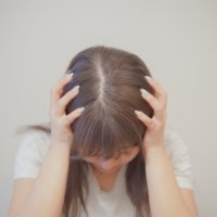 頭を抱えて塞ぎ込む女性